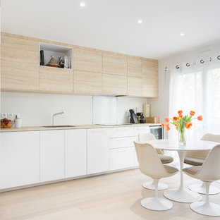 Mid-sized scandinavian eat-in kitchen inspiration - Inspiration for a mid-sized scandinavian single-wall light wood floor and beige floor eat-in kitchen remodel in Paris with flat-panel cabinets, white cabinets, laminate countertops, white backsplash, glass sheet backsplash, no island, an undermount sink, paneled appliances and beige countertops