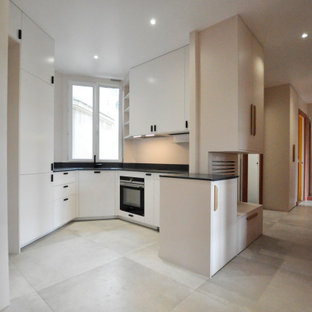 Design ideas for a small transitional u-shaped open plan kitchen in Paris with an integrated sink, beaded inset cabinets, white cabinets, solid surface benchtops, blue splashback, black appliances, ceramic floors, grey floor and blue benchtop.