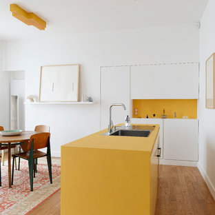 Imagen de cocina comedor lineal, actual, pequeña, con fregadero de un seno, armarios con paneles lisos, puertas de armario blancas, salpicadero amarillo, suelo de madera clara, una isla y encimeras amarillas