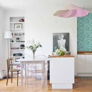 Réalisation d'une cuisine design avec un évier posé, un placard à porte plane, des portes de placard blanches, une crédence bleue, un sol en bois brun et une péninsule.