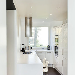 This is an example of a small contemporary u-shaped separate kitchen in Paris with stainless steel appliances, ceramic floors, no island, flat-panel cabinets and white cabinets.