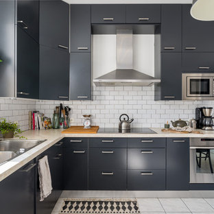 This is an example of a large scandinavian l-shaped eat-in kitchen in Lyon with a double-bowl sink, black cabinets, white splashback, stainless steel appliances, ceramic floors and no island.
