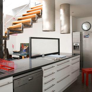 Aménagement d'une cuisine américaine linéaire industrielle de taille moyenne avec un évier encastré, un placard à porte plane, des portes de placard blanches, une crédence en feuille de verre, un électroménager en acier inoxydable, béton au sol et un îlot central.