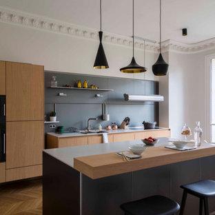 Réalisation d'une grande cuisine linéaire design fermée avec un évier encastré, un placard à porte plane, des portes de placard en bois clair, une crédence grise, un électroménager encastrable, un sol en bois clair, un îlot central, un sol beige et un plan de travail blanc.