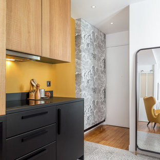 This is an example of a contemporary kitchen in Paris with flat-panel cabinets, black cabinets, yellow splashback, multi-coloured floor and black benchtop.