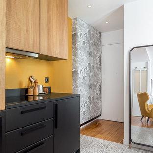 Inspiration pour une cuisine design avec un placard à porte plane, des portes de placard noires, une crédence jaune, un sol multicolore et un plan de travail noir.