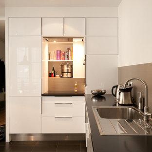 Exemple d'une cuisine tendance en L fermée et de taille moyenne avec un évier posé, un placard à porte plane, des portes de placard blanches, une crédence grise et aucun îlot.