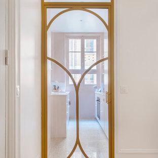 パリの小さいシャビーシック調のおしゃれなキッチン (アンダーカウンターシンク、インセット扉のキャビネット、ピンクのキャビネット、珪岩カウンター、白いキッチンパネル、テラコッタタイルのキッチンパネル、パネルと同色の調理設備、テラゾーの床、アイランドなし、白い床、ピンクのキッチンカウンター) の写真