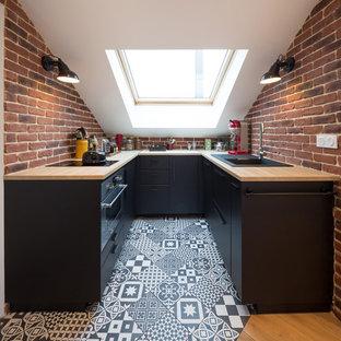 Inspiration pour une cuisine américaine nordique avec un évier posé, un placard à porte plane, des portes de placard noires, un plan de travail en bois, une crédence rouge, une crédence en brique, un électroménager noir, un sol en carreaux de ciment, un sol multicolore et un plan de travail marron.