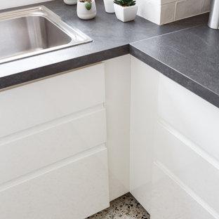 Modern inredning av ett avskilt, litet svart linjärt svart kök, med en undermonterad diskho, släta luckor, vita skåp, bänkskiva i koppar, vitt stänkskydd, stänkskydd i tunnelbanekakel, rostfria vitvaror, terrazzogolv, en köksö och flerfärgat golv
