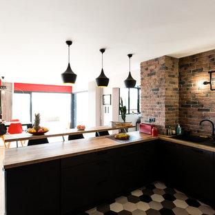 モンペリエのコンテンポラリースタイルのおしゃれなLDK (シングルシンク、黒いキャビネット、木材カウンター、カラー調理設備、セラミックタイルの床、マルチカラーの床、レンガのキッチンパネル) の写真