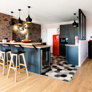 モンペリエのコンテンポラリースタイルのおしゃれなダイニングキッチン (シングルシンク、木材カウンター、カラー調理設備、セラミックタイルの床、マルチカラーの床、黒いキャビネット、レンガのキッチンパネル) の写真
