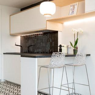 パリの小さい北欧スタイルのおしゃれなキッチン (アンダーカウンターシンク、白いキャビネット、ラミネートカウンター、黒いキッチンパネル、テラコッタタイルのキッチンパネル、パネルと同色の調理設備、セメントタイルの床、アイランドなし、白い床、フラットパネル扉のキャビネット) の写真