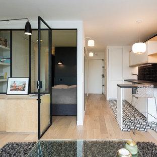 Small scandinavian single-wall open plan kitchen in Paris with an undermount sink, white cabinets, laminate benchtops, black splashback, terra-cotta splashback, panelled appliances, cement tiles, no island, white floor and flat-panel cabinets.