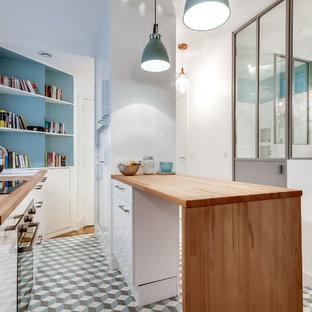 Réalisation d'une petite cuisine ouverte parallèle nordique avec un évier 1 bac, un placard à porte plane, des portes de placard blanches, un plan de travail en bois, un électroménager en acier inoxydable, un sol en carreaux de ciment et un îlot central.