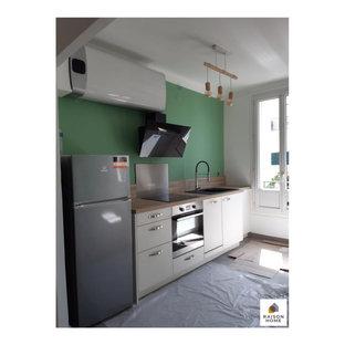 Réalisation d'une petit cuisine ouverte linéaire minimaliste avec un évier encastré, un placard à porte plane, des portes de placard blanches, un plan de travail en bois, une crédence marron, une crédence en bois, un électroménager encastrable, un sol en carreaux de ciment, un îlot central, un sol gris, un plan de travail marron et un plafond en papier peint.