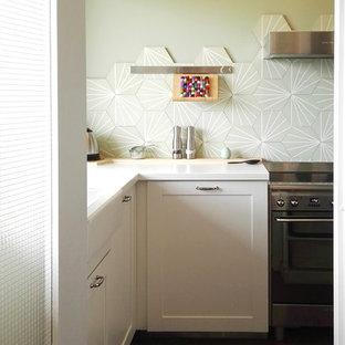 パリの小さいミッドセンチュリースタイルのおしゃれなキッチン (エプロンフロントシンク、ガラス扉のキャビネット、白いキャビネット、ラミネートカウンター、緑のキッチンパネル、セメントタイルのキッチンパネル、シルバーの調理設備の、テラコッタタイルの床、アイランドなし、赤い床) の写真