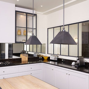 This is an example of a large contemporary single-wall open plan kitchen in Paris with an integrated sink, light wood cabinets, granite worktops, black splashback, mirror splashback, stainless steel appliances, an island and black worktops.