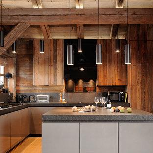Aménagement d'une cuisine américaine montagne en L de taille moyenne avec un évier 2 bacs, un placard à porte plane, des portes de placard en bois brun, une crédence grise, un sol en bois clair, un îlot central et un électroménager de couleur.