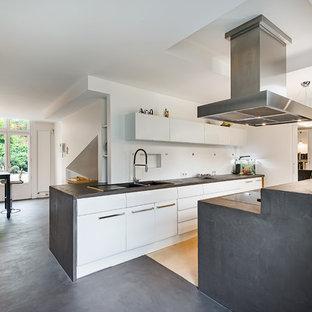 Idées déco pour une grande cuisine ouverte contemporaine en L avec des portes de placard blanches, un plan de travail en béton, une crédence blanche, béton au sol, un îlot central, un évier intégré, un placard à porte plane et un électroménager blanc.