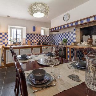 Aménagement d'une cuisine ouverte campagne en L de taille moyenne avec un évier intégré, des portes de placard en bois clair, un plan de travail en carrelage, une crédence bleue, une crédence en mosaïque et aucun îlot.