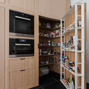 Immagine di un'ampia cucina nordica con lavello integrato, ante a filo, ante in legno chiaro, top in acciaio inossidabile, paraspruzzi nero, paraspruzzi in ardesia, elettrodomestici da incasso, pavimento in ardesia, isola e pavimento nero
