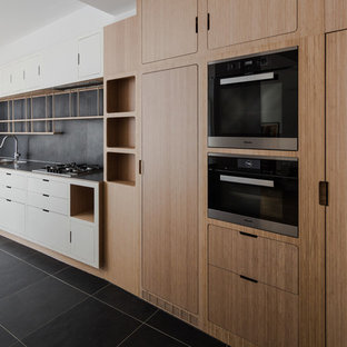 This is an example of an expansive scandinavian galley eat-in kitchen in Paris with an integrated sink, beaded inset cabinets, light wood cabinets, stainless steel benchtops, black splashback, slate splashback, panelled appliances, slate floors, with island and black floor.