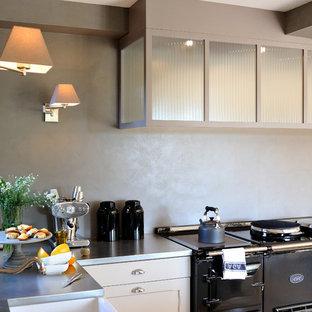 Exemple d'une cuisine américaine éclectique en L avec un plan de travail en inox, une crédence grise, un électroménager en acier inoxydable et aucun îlot.