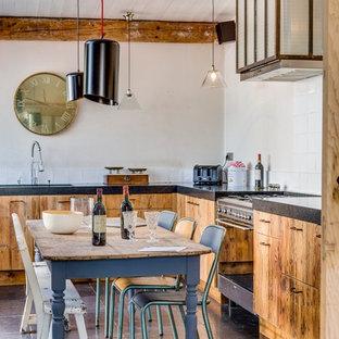 Exemple d'une cuisine américaine éclectique en L de taille moyenne avec un placard à porte plane, des portes de placard en bois clair, une crédence blanche, aucun îlot, un évier encastré, une crédence en carreau de ciment et un électroménager noir.