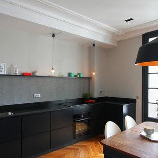Inspiration pour une cuisine américaine design en L de taille moyenne avec des portes de placard noires, aucun îlot et une crédence grise.