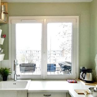 パリの小さいミッドセンチュリースタイルのおしゃれなキッチン (エプロンフロントシンク、ガラス扉のキャビネット、白いキャビネット、ラミネートカウンター、緑のキッチンパネル、セメントタイルのキッチンパネル、シルバーの調理設備、テラコッタタイルの床、アイランドなし、赤い床) の写真