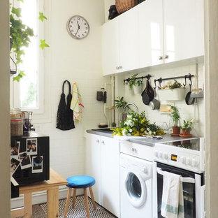 Inredning av ett modernt litet grå linjärt grått kök, med vita skåp, vitt stänkskydd, terrazzogolv, grått golv, en nedsänkt diskho, släta luckor och vita vitvaror