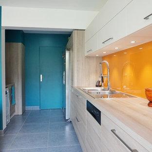 パリの大きいコンテンポラリースタイルのおしゃれなキッチン (アンダーカウンターシンク、淡色木目調キャビネット、黄色いキッチンパネル) の写真