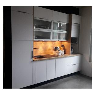 パリの小さい北欧スタイルのおしゃれなキッチン (アンダーカウンターシンク、フラットパネル扉のキャビネット、ステンレスキャビネット、木材カウンター、茶色いキッチンパネル、木材のキッチンパネル、シルバーの調理設備、コンクリートの床、グレーの床、茶色いキッチンカウンター、クロスの天井) の写真