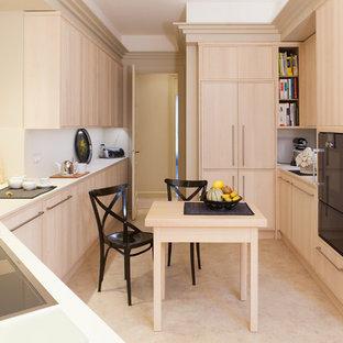 Exemple d'une cuisine américaine moderne en U de taille moyenne avec des portes de placard en bois clair, un plan de travail en quartz, une crédence blanche, un placard à porte plane, un électroménager noir et aucun îlot.