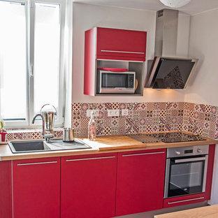 ナントの中くらいのモダンスタイルのおしゃれなキッチン (シングルシンク、ラミネートカウンター、パネルと同色の調理設備、セラミックタイルの床、グレーの床、赤いキャビネット、マルチカラーのキッチンパネル、茶色いキッチンカウンター) の写真