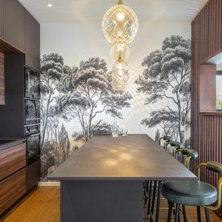 Aménagement d'une cuisine parallèle contemporaine avec un placard à porte plane, des portes de placard en bois sombre, une crédence verte, un électroménager noir, un sol en bois brun, une péninsule, un sol marron, un plan de travail gris et un plafond en papier peint.
