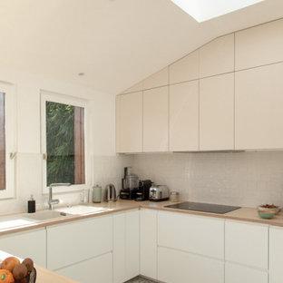 パリの広いモダンスタイルのおしゃれなキッチン (ドロップインシンク、フラットパネル扉のキャビネット、白いキャビネット、木材カウンター、ベージュキッチンパネル、テラコッタタイルのキッチンパネル、パネルと同色の調理設備、テラゾーの床、マルチカラーの床、ベージュのキッチンカウンター) の写真