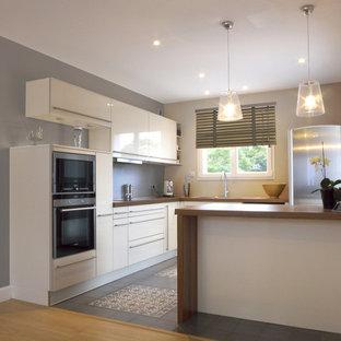 Exemple d'une cuisine tendance en L de taille moyenne et fermée avec des portes de placard blanches, un plan de travail en stratifié, un électroménager encastrable, un sol en carreaux de ciment et un îlot central.