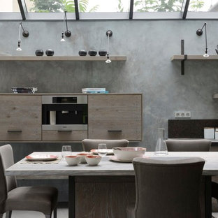 Aménagement d'une grande cuisine américaine linéaire contemporaine avec des portes de placard en bois brun et un îlot central.