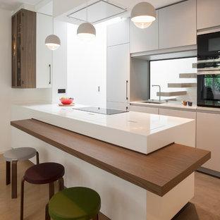 Réalisation d'une cuisine design avec un évier encastré, un placard à porte plane, des portes de placard blanches, une crédence en fenêtre, un électroménager noir, une péninsule, un sol marron et un plan de travail blanc.
