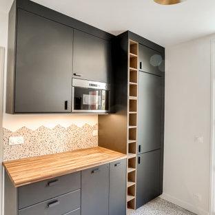 На фото: отдельная, параллельная кухня среднего размера в стиле ретро с двойной раковиной, плоскими фасадами, черными фасадами, столешницей из бетона, разноцветным фартуком, фартуком из керамогранитной плитки, техникой под мебельный фасад, полом из керамической плитки, разноцветным полом и зеленой столешницей без острова с