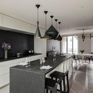 Aménagement d'une grande cuisine américaine parallèle contemporaine avec un évier encastré, des portes de placard blanches, une crédence noire, un électroménager encastrable, un sol en bois brun et un îlot central.