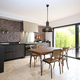 Immagine di una cucina mediterranea con lavello a vasca singola, ante lisce, ante in legno bruno, paraspruzzi rosso, paraspruzzi in mattoni, elettrodomestici neri, nessuna isola e pavimento beige