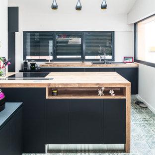 Réalisation d'une grande cuisine ouverte design en U avec un évier 2 bacs, un placard avec porte à panneau encastré, des portes de placard noires, un plan de travail en bois, un électroménager encastrable, un sol en carrelage de céramique et un îlot central.
