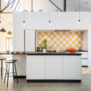 Cette photo montre une cuisine américaine parallèle tendance de taille moyenne avec une crédence en carreau de céramique, un îlot central, un placard à porte plane, des portes de placard blanches et une crédence multicolore.
