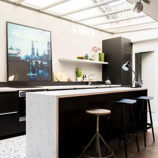 Aménagement d'une cuisine parallèle contemporaine avec un placard à porte plane, des portes de placard noires, un sol en bois clair, un îlot central, un sol beige et un plan de travail blanc.