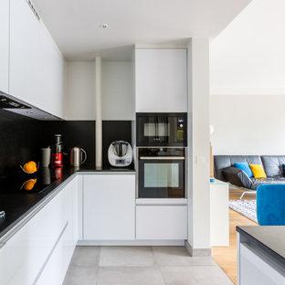 Cette image montre une cuisine design en U avec un évier encastré, un placard à porte plane, des portes de placard blanches, une crédence noire, un électroménager noir, un îlot central, un sol gris et un plan de travail noir.