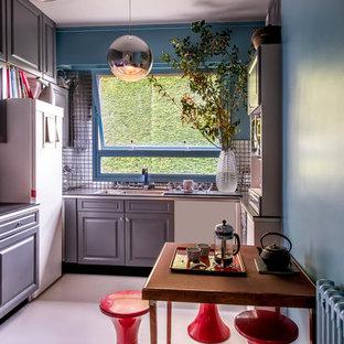 Foto de cocina comedor en L, bohemia, de tamaño medio, sin isla, con fregadero de doble seno, armarios con paneles con relieve, puertas de armario grises, salpicadero de metal y electrodomésticos blancos