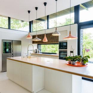 Aménagement d'une cuisine contemporaine en L avec un placard à porte plane, des portes de placard blanches, une crédence en fenêtre, un électroménager en acier inoxydable, un îlot central, un sol blanc, un plan de travail blanc, un évier encastré, un plan de travail en surface solide et béton au sol.
